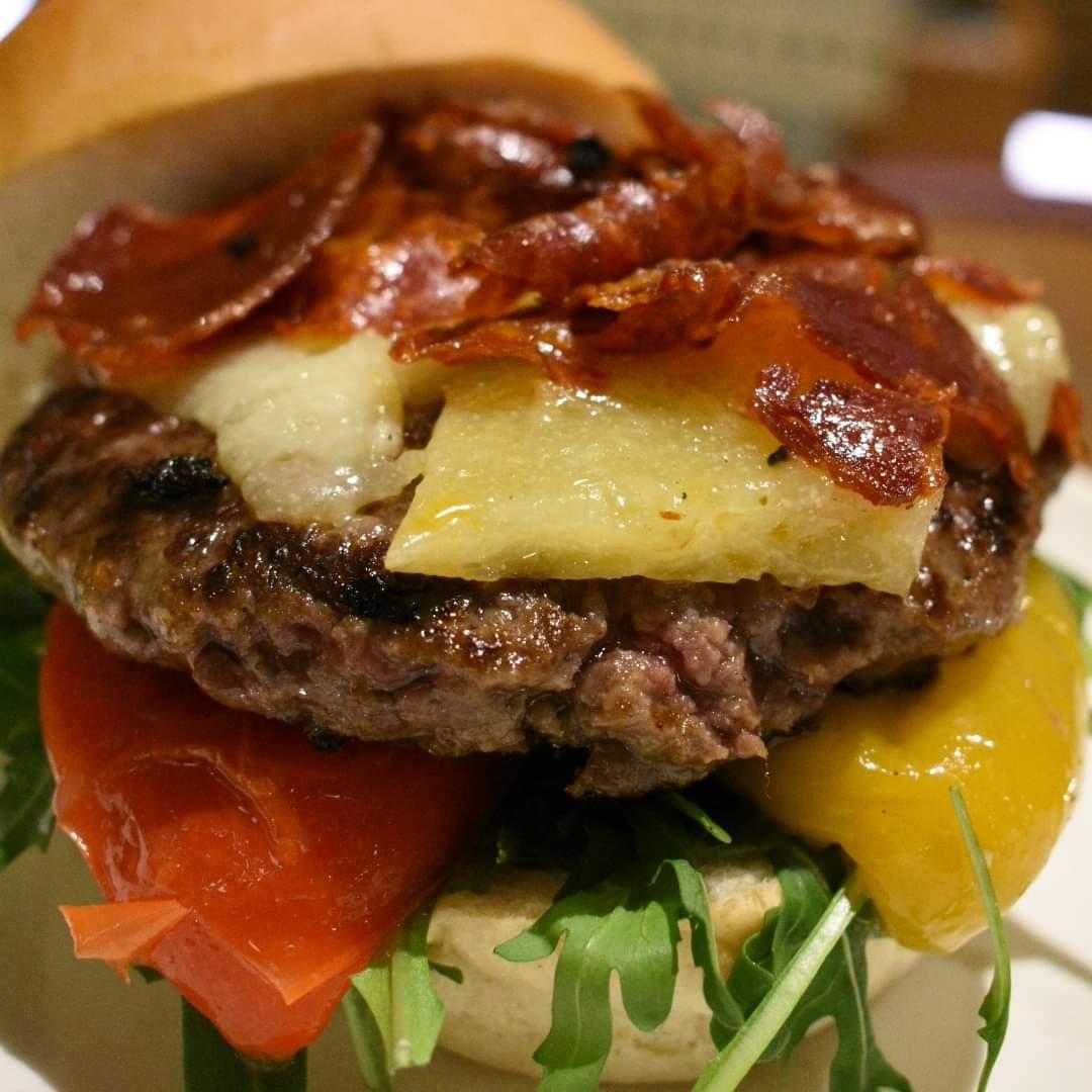 immagine Hamburger, rucola, peperoni cotti a bassa temperatura, formaggio ubriaco, chips di salame spagnolo cotto al forno e pane.